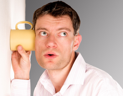 Man listening through the wall with the cup